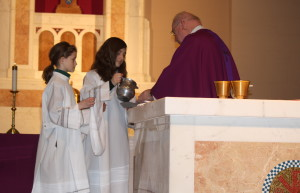 Altar Servers helping prepare The Eucharist during Mass.